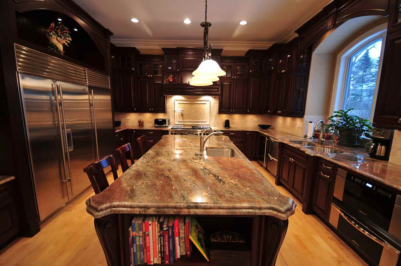 featured image on a blog regarding countertop edge profiles. This image depicts a kitchen with dark wood cabinetry and a long island in the middle with a granite countertop