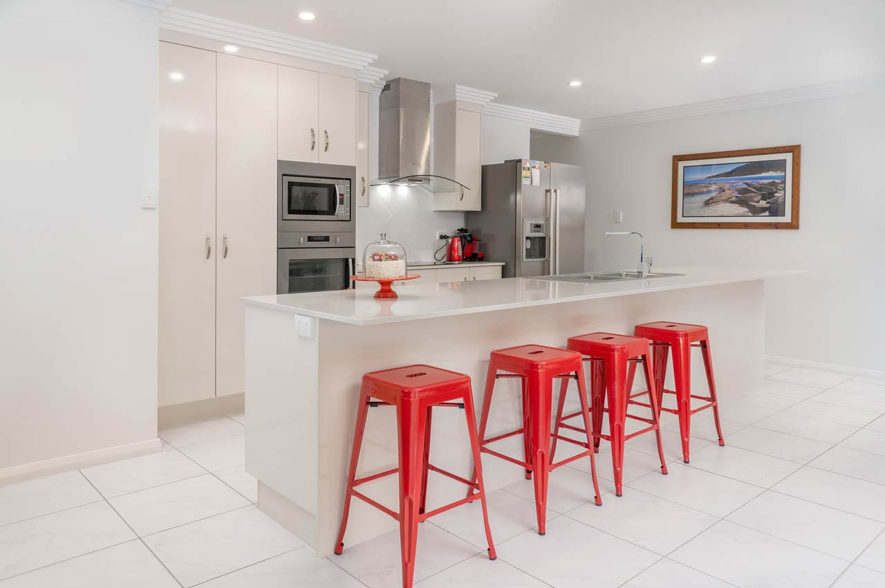 """in our blog about countertop edge profile, this depicts a kitchen island with a while and red aesthetic. the counterop extends out on the opposite side to act as a """"bar"""" area."""