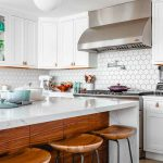 Modern kitchen with white quartz countertops and woodgrain cabinets for use in blog post about cost of countertops.