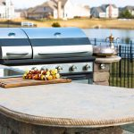 Image of an outdoor kitchen with a grill, sink, and granite countertops.